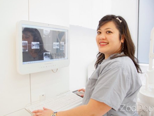 Picture of Dr Julie Wee in front of dental computer.